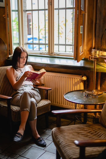 Woman reading book while sitting on chair at home