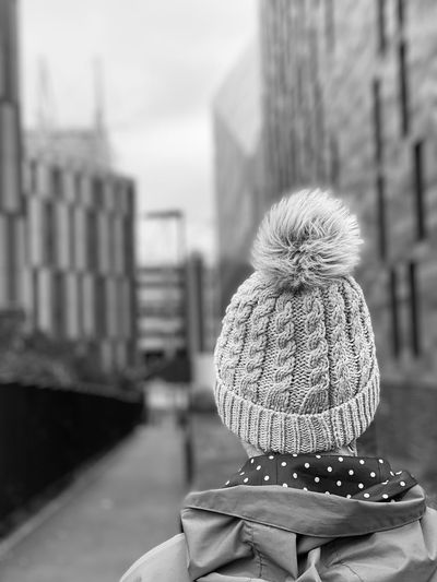 Rear view of woman in hat against buildings in city