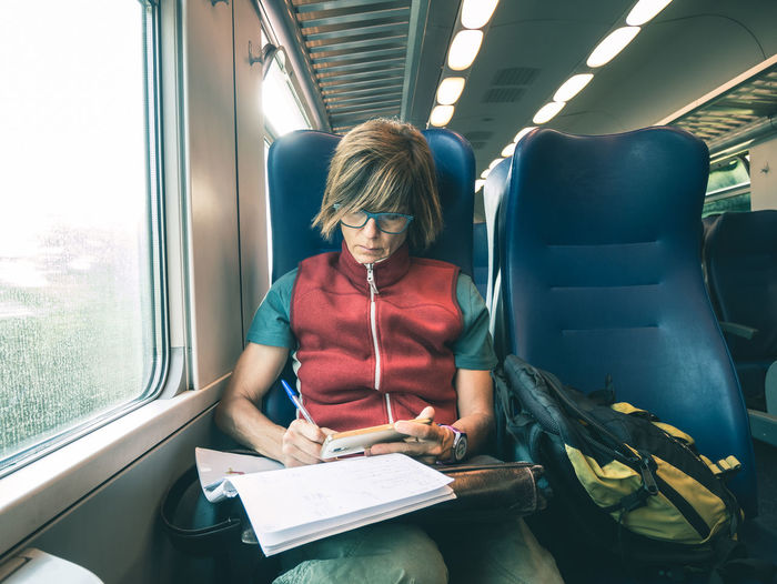 Woman writing on book while traveling in train