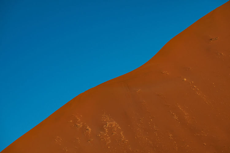 Sand dune profile against blue sky in namib desert