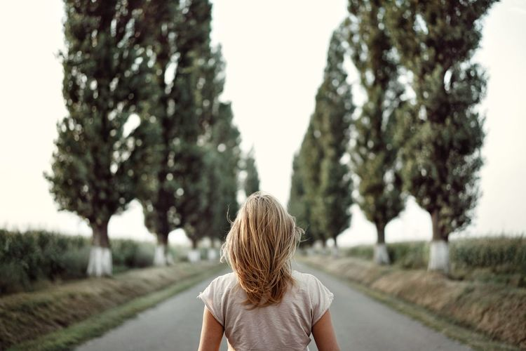 Rear view of woman on road against clear sky