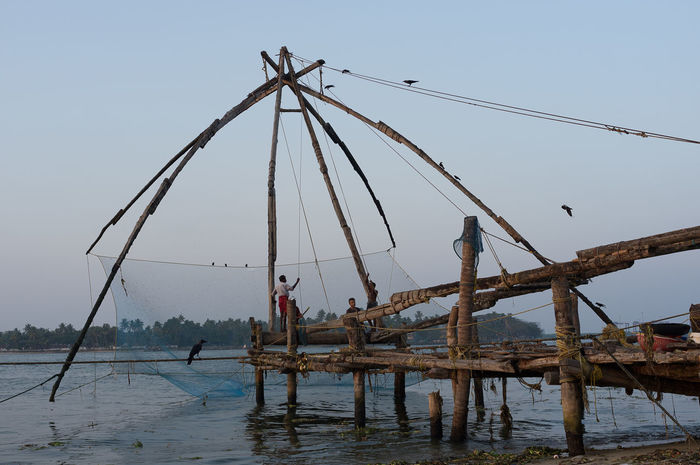 Chinese fishing nets in the evening in Kochi, India Clear Sky Fisherman Fishing Fishing Equipment Fishing Net India Kerala Kochi Men Nature Nautical Vessel Occupation Outdoors Real People Sea Sky Water Wooden Raft