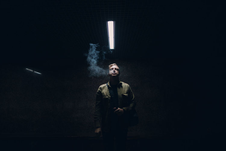 Portrait of young man smoking cigarette against black background