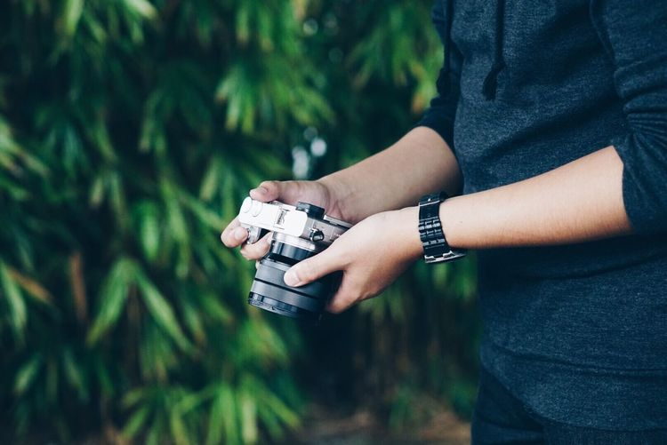 Midsection of man holding camera against tree