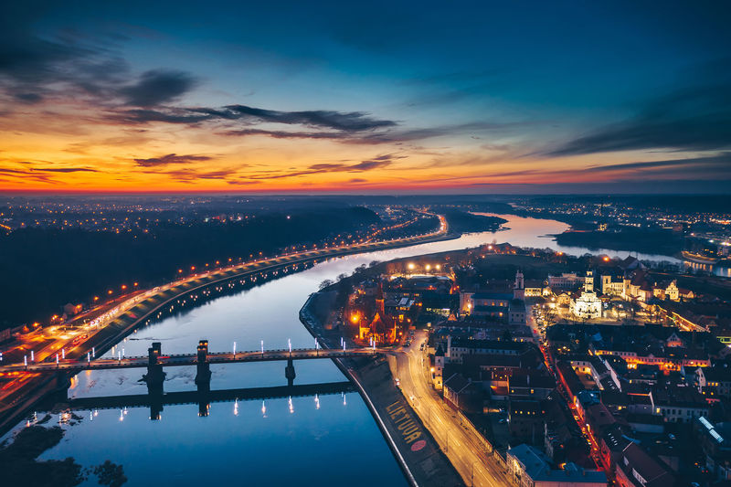 Aerial view of illuminated bridge over river in city at sunset