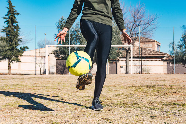 Low section of man playing soccer ball against sky