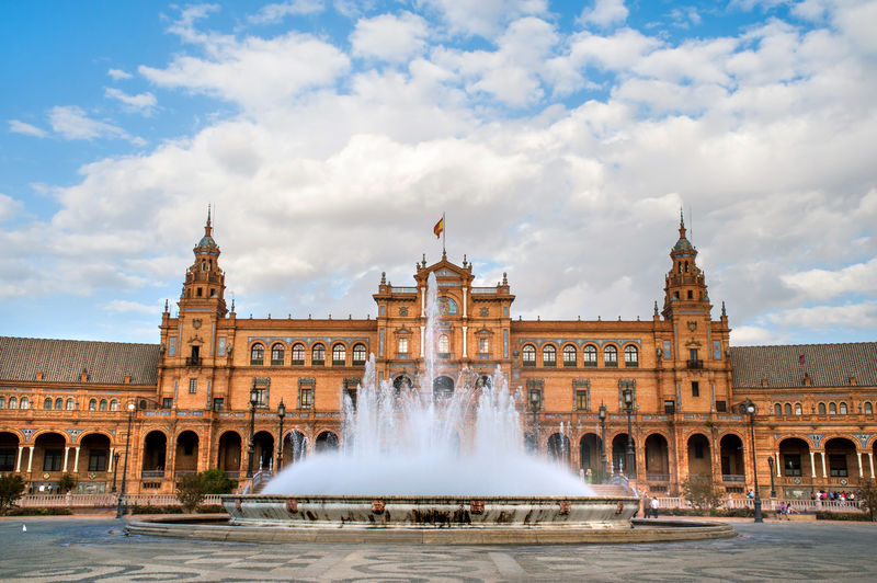 Fountain outside plaza de espana against cloudy sky