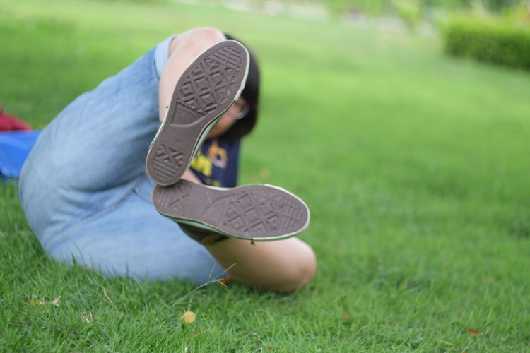 Person showing soles of shoes while lying on grassy field