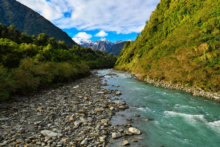River flowing amidst mountains against sky