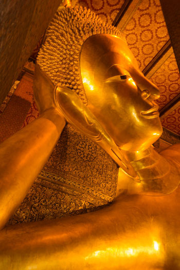 A Part of Buddha statue at Wat Pho in Bangkok, Thailand Statue Sculpture Human Representation Male Likeness Representation Gold Colored Art And Craft Religion Spirituality Belief Architecture Low Angle View Creativity Place Of Worship Building Indoors  Built Structure No People Idol Gold Buddha Statue Bangkok Thailand. Wat Po Royal Temple Asian Temple Bangkok Temples EyeEmNewHere