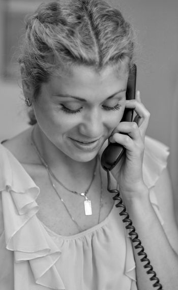 Smiling woman talking on telephone at home
