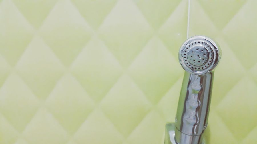 Close-up of shower by wall in bathroom