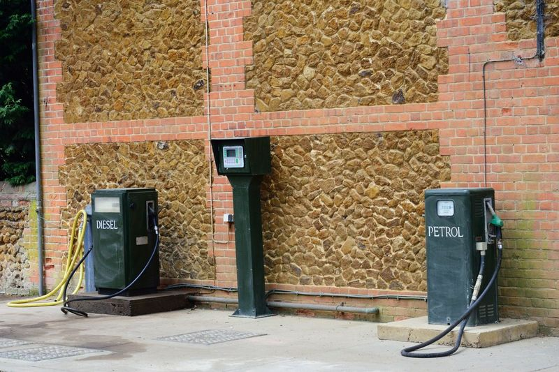 Vintage petrol pumps standing on forecourt Fuel And Power Generation Petrol Vintage Old Green Brick Red Old Fashioned Pumps Gas