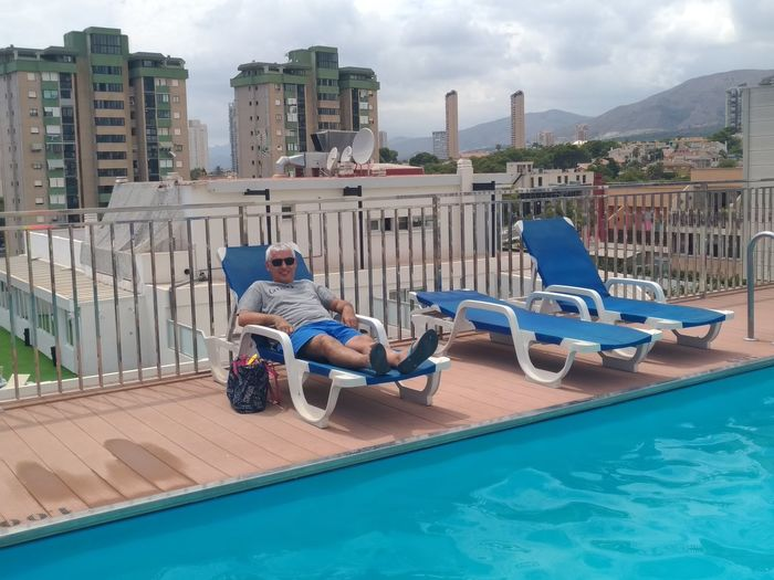 Portrait Of Man Relaxing On Lounge Chair At Poolside In City