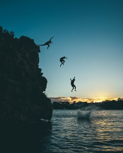 Silhouette men jumping from cliff into sea during sunset