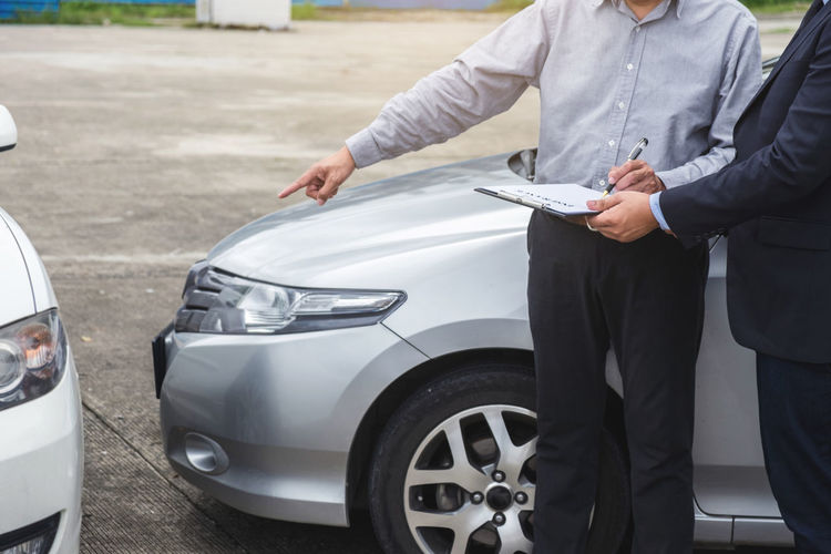 Midsection of customer pointing at car while signing insurance contract