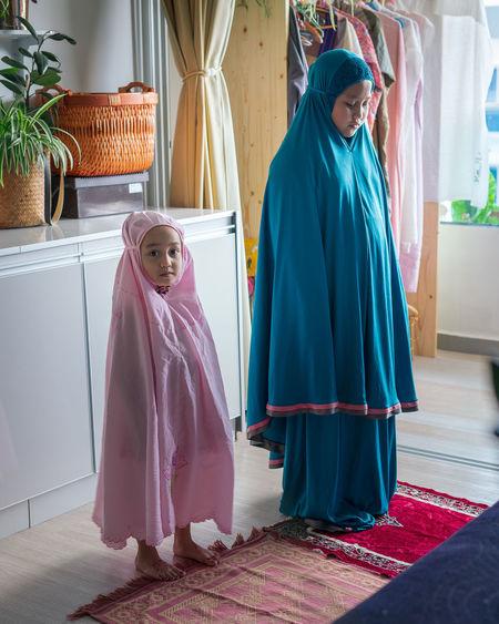 Rear view of women looking at camera at home
