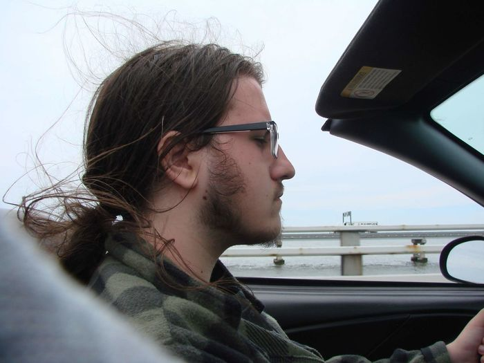 Portrait of young man looking through car. driving top down road trip