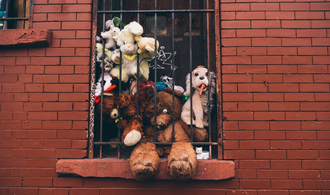 Stuffed toys in window of brick wall
