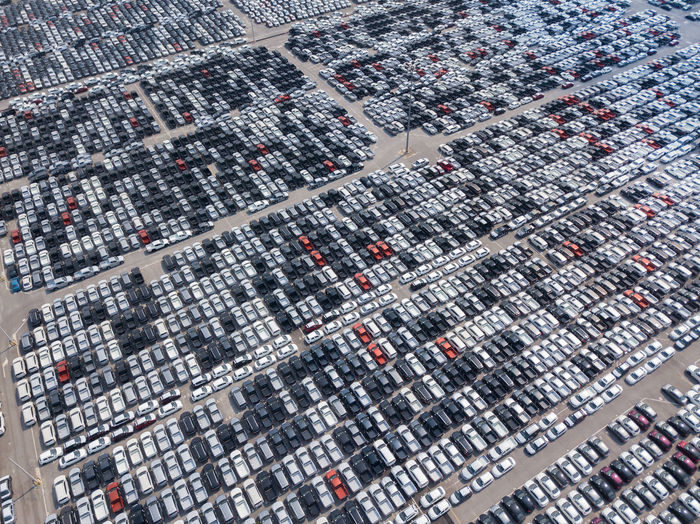 Aerial View of new cars parked at the parking area of automobile factory. Waiting for export and import at the international port. Aerial View Transportation High Angle View Motor Vehicle Car Industry Modern Business Parking Lot Luxury Mode Of Transportation Import Export New Car Business