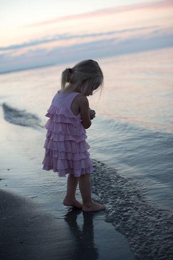 Playful girl at beach against sky