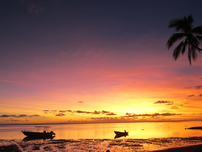 Silhouette Boats Moored In Sea Against Sky During Sunset