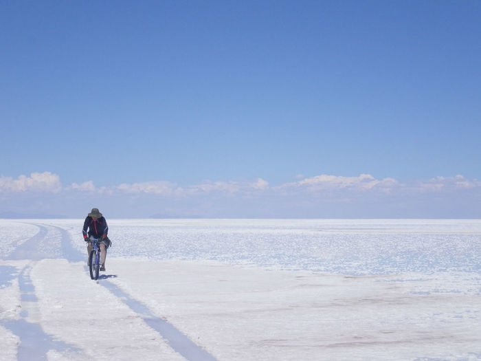Man Adult Beauty In Nature Bike Cloud - Sky Copy Space Day Full Length Horizon Horizon Over Water Land Leisure Activity Nature One Person Outdoors Rear View Salar De Uyuni Scenics - Nature Sky Standing Tranquility Water