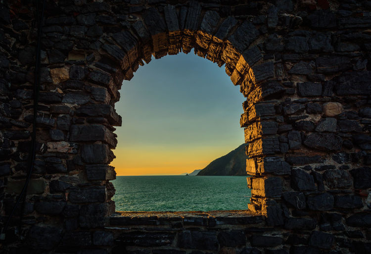 View of sea through arch window at sunset
