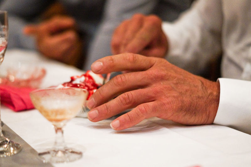 Midsection Of Man Holding Ice Cream On Table