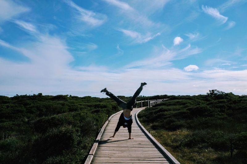Full length of man using handstand on boardwalk against sky