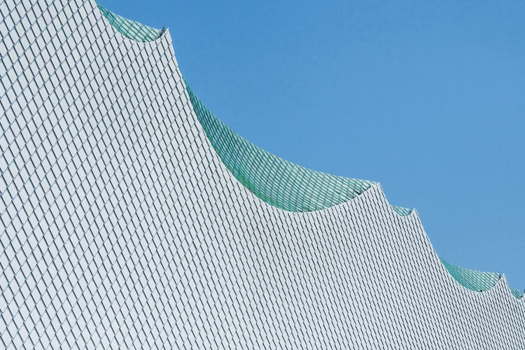 Low angle view of white modern building against clear blue sky