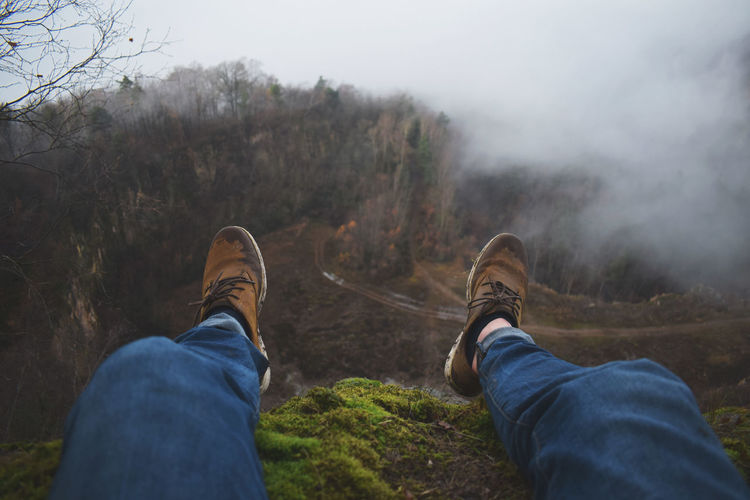 Adult Adventure Bare Tree Beauty In Nature Cliff Danger Day EyeEm Best Shots Fog Grass Hiking Human Body Part Human Leg Landscape Leisure Activity Lifestyles Low Section Men Nature Outdoors People Real People Scenics Shoe Sky
