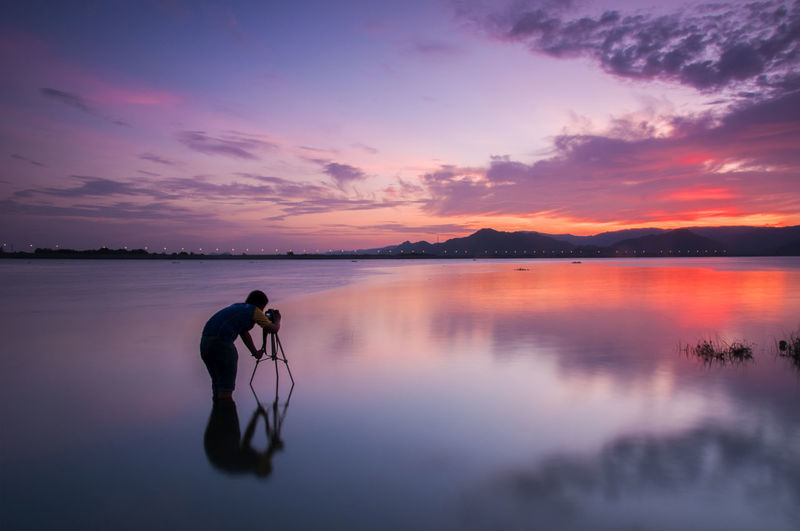 Man photographing while standing in lake during sunset