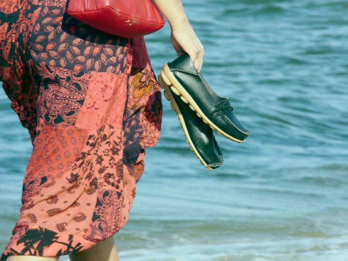 Midsection of woman wading in sea