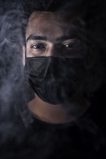 Portrait of young man wearing mask amidst smoke