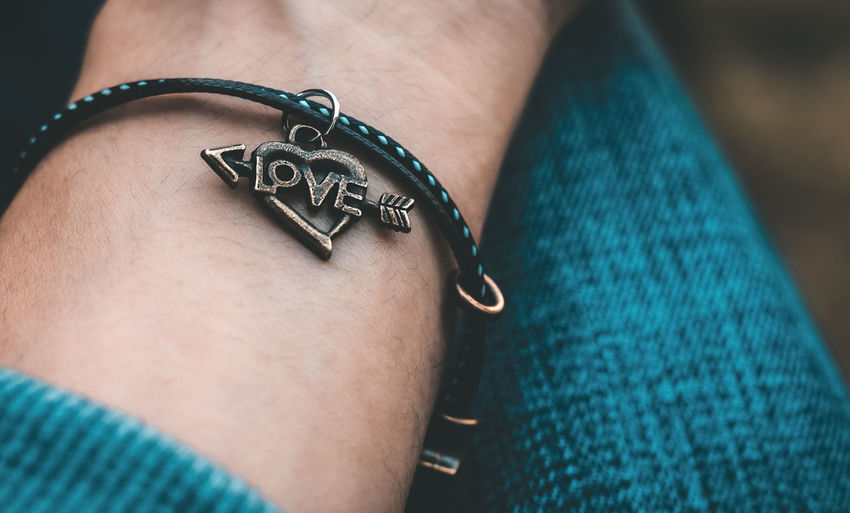 Close-up of person wearing bracelet with love text