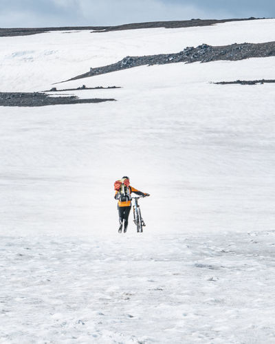 Rear view of man skiing on frozen land