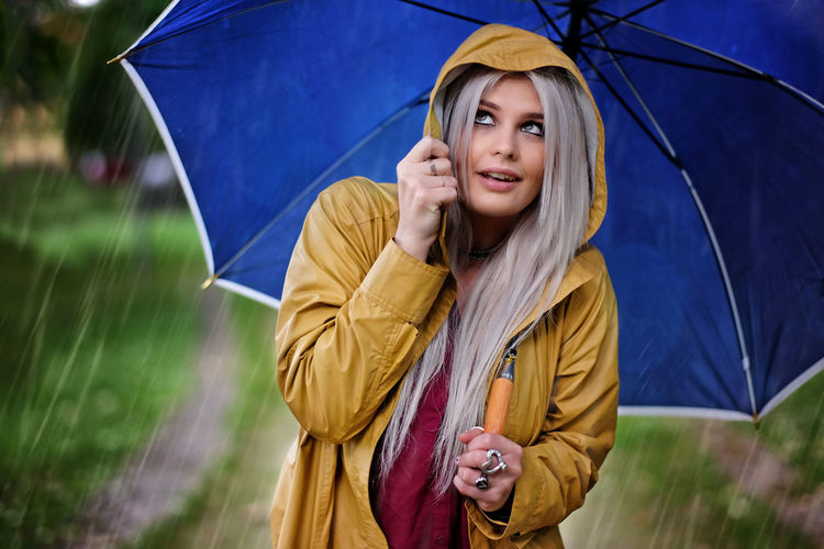 Portrait Of Young Woman Holding Umbrella In Rain