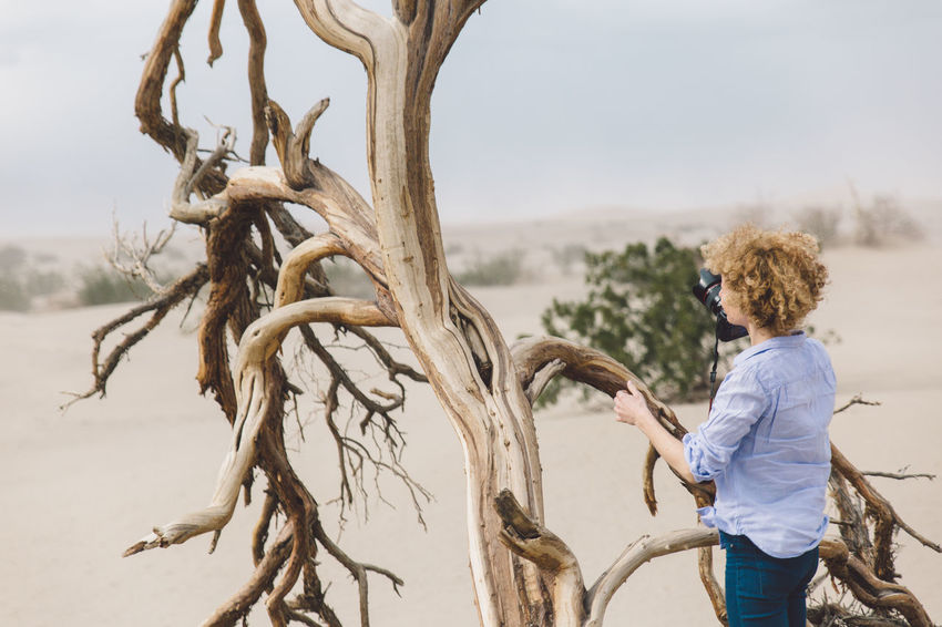 Arid Climate Arid Landscape Curly Hair Day Death Valley Death Valley National Park Desert Dunes Girl Lifestyles Nature One Person Outdoors People Real People Sand Dune Sand Storm Sky Standing Storm Tree Tree Trunk