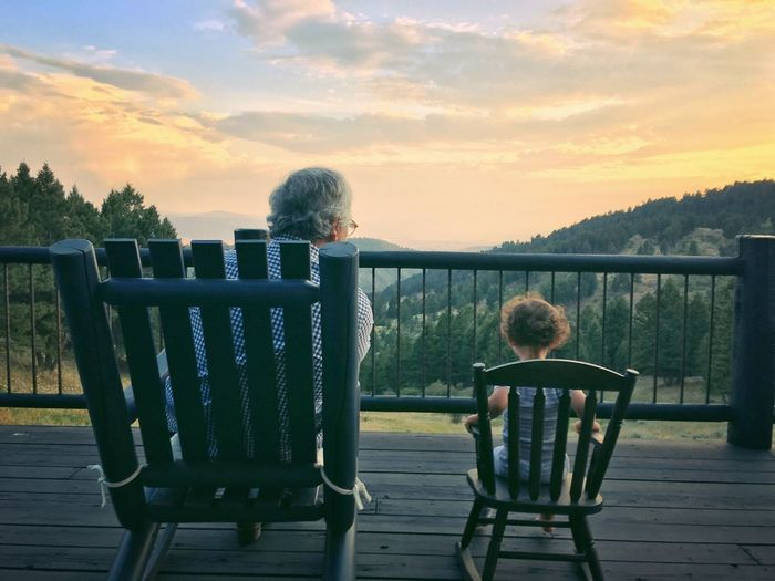 Grandfather With Granddaughter Sitting On Chair At Observation Point Against Cloudy Sky During Sunset
