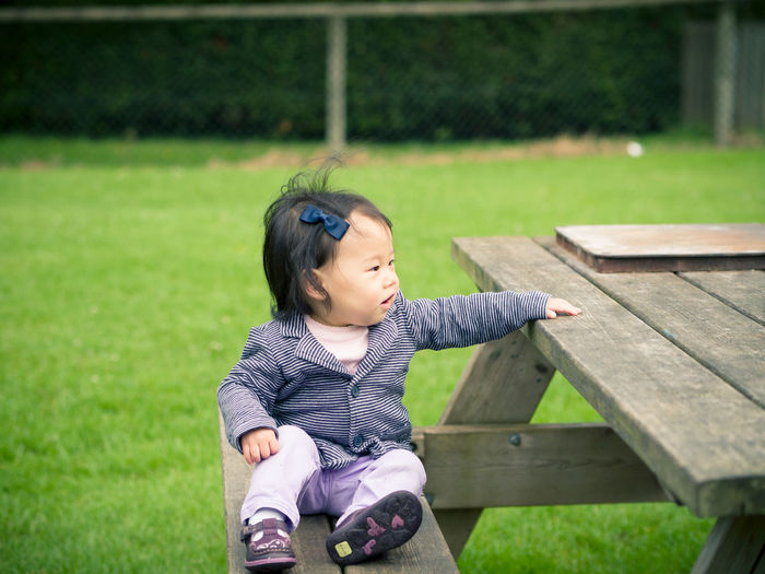 Baby girl looking away while sitting on picnic table outdoors