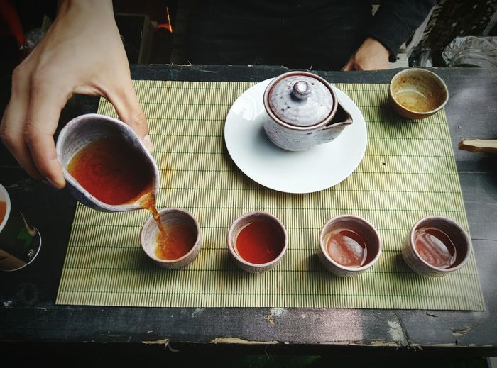 Cropped image of person pouring chinese tea in cup on table