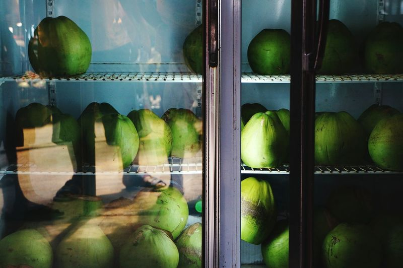 Coconuts in refrigerator at store