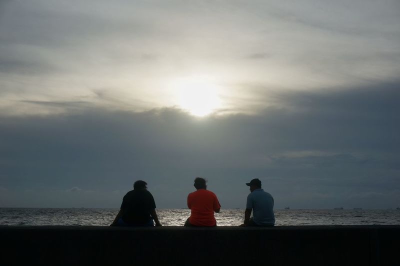 Silhouette of people sitting on beach