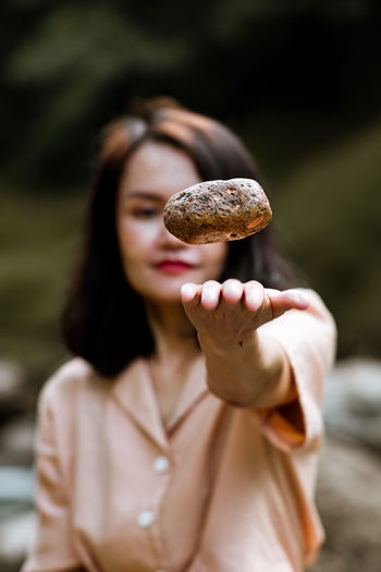 Close-up of woman throwing potato in air outdoors