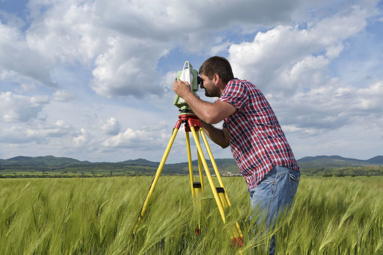 Land surveyor in a wheat field Agriculture Field Industry Station Sunny Wheat Working Caucasian Clouds Engineer Equipment Geodesy Internet Landsurveyor Location Measurement Network Occupation One Man Only Point Professional Spring Summer Technology Tripod