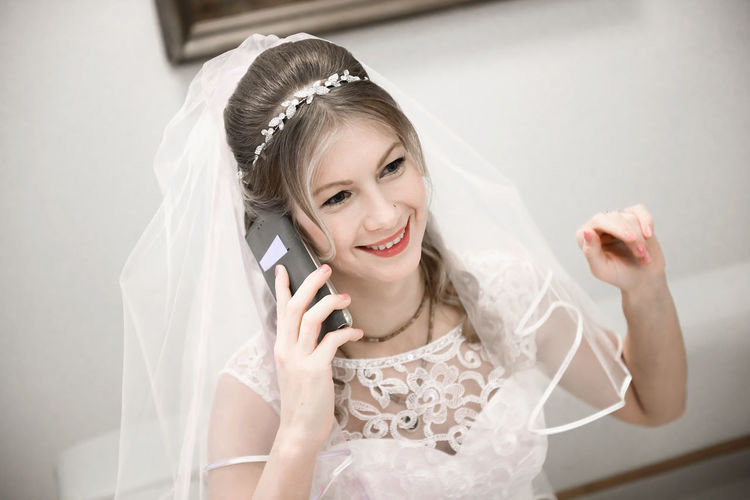 Bride Talking On Phone While Sitting On Sofa