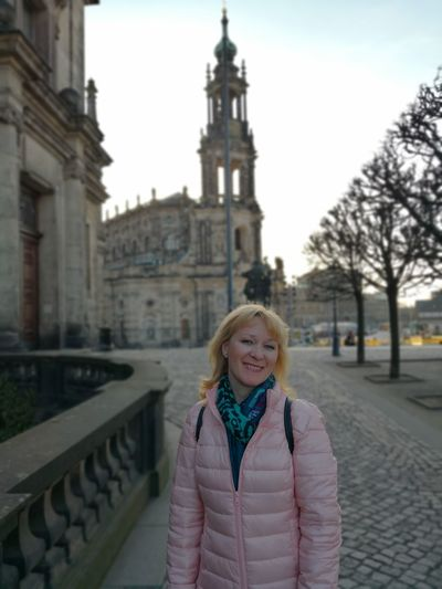 Portrait of smiling mature woman standing on street against cathedral in town