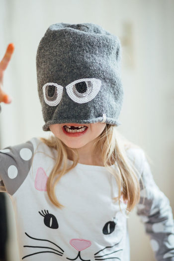 Knitted Hat Eyes Funny Faces Obscured Face Indoors  Innocence Cute Leisure Activity Lifestyles Happiness Real People Girls Headshot Focus On Foreground Front View Portrait One Person Child Childhood Missing Tooth School Children Preschooler Teeth