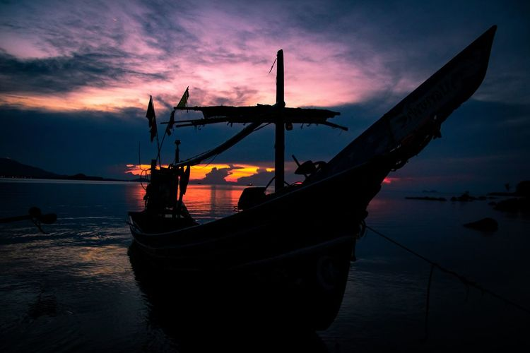 View of fishing boat in sea during sunset